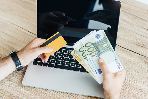 신용 카드와 노트북 위에 돈을 들고 사람의 자른된 샷 금융에 대한 스톡 사진 및 기타 이미지