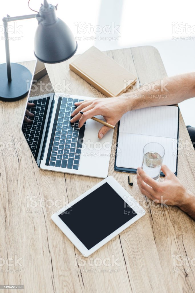 cropped shot of person holding glass of water and using laptop at workplace royalty-free stock photo