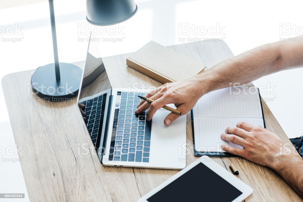 cropped shot of person holding pen, using laptop and taking notes at workplace royalty-free stock photo
