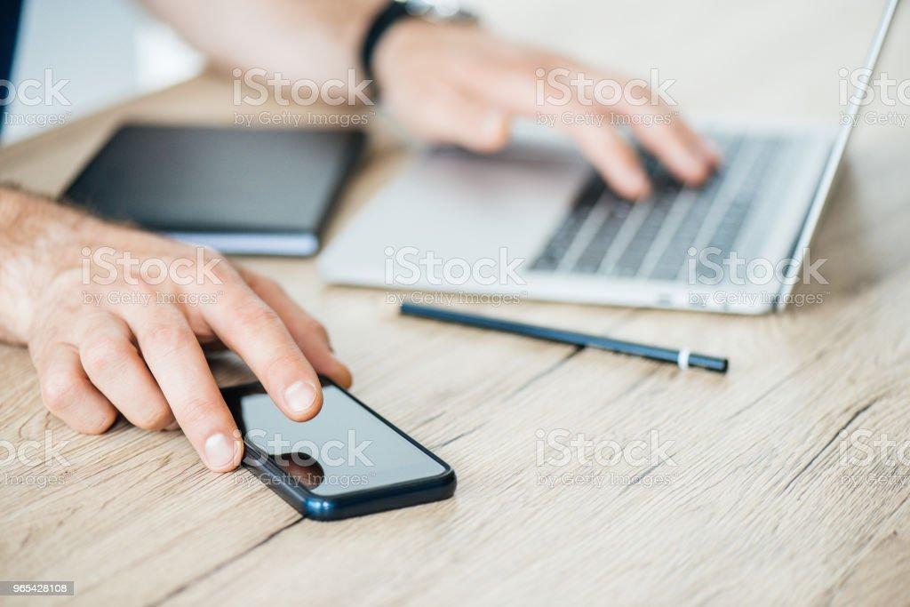 photo recadrée de personne tenant smartphone et utilisez l'ordinateur portable à une table en bois - Photo de Affaires libre de droits