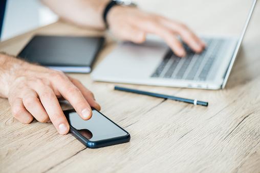 사람의 스마트폰 들고 나무 테이블에서 노트북을 사용 하 여 자른된 샷 기술자에 대한 스톡 사진 및 기타 이미지