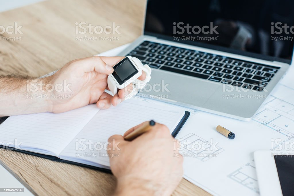 cropped shot of person holding smartwatch and taking notes at workplace zbiór zdjęć royalty-free