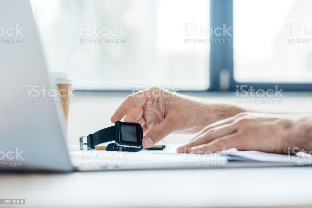cropped shot of person holding smartwatch and using laptop at workplace royalty-free stock photo