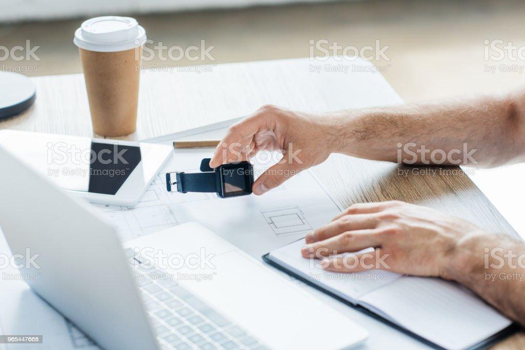 recadrée tir de personne tenant smartwatch et travaillant à table - Photo de Application mobile libre de droits