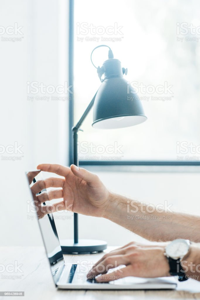 cropped shot of person using laptop at workplace royalty-free stock photo