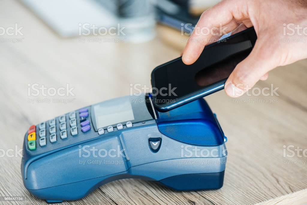 cropped shot of person using smartphone and payment terminal royalty-free stock photo