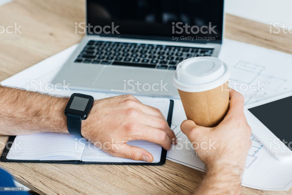 cropped shot of person wearing smartwacth and holding disposable coffee cup at workplace zbiór zdjęć royalty-free