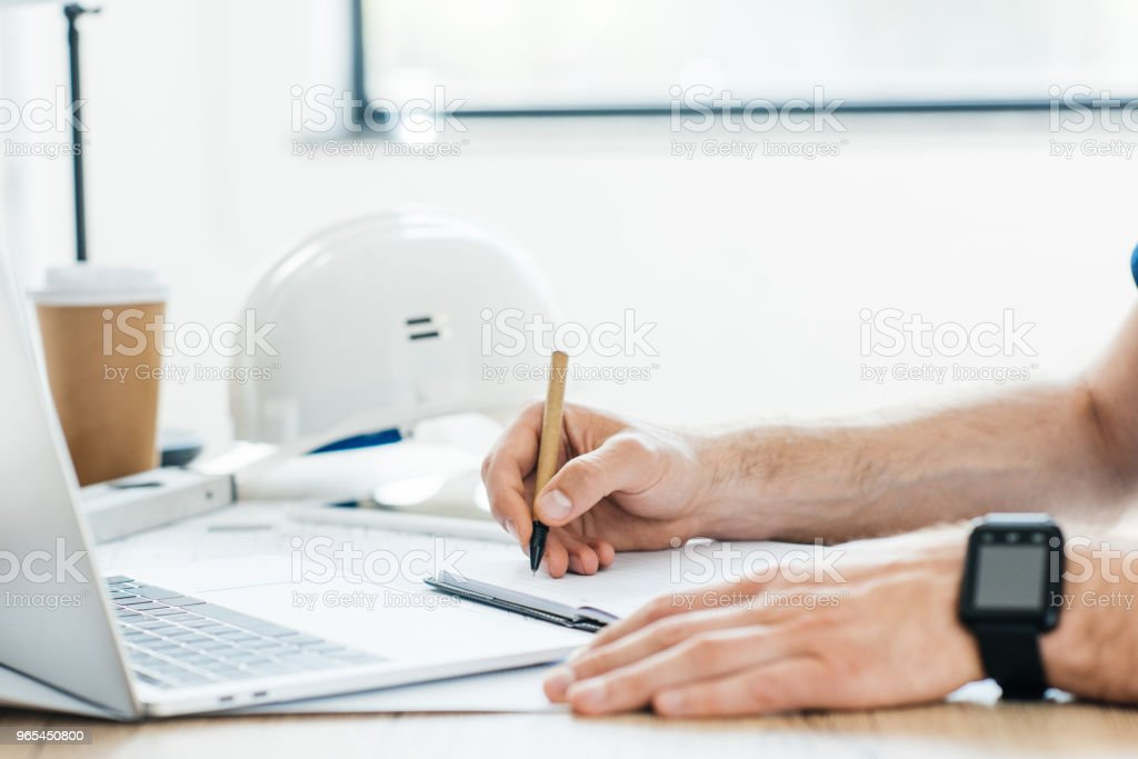 cropped shot of person wearing smartwatch and taking notes at workplace royalty-free stock photo