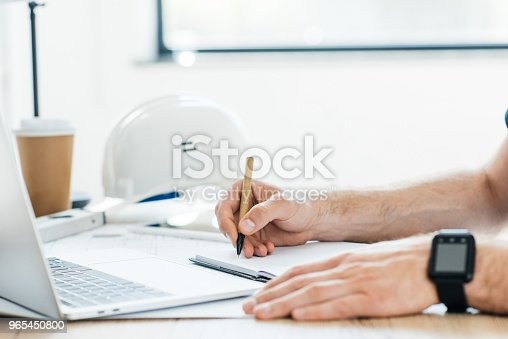 Cropped Shot Of Person Wearing Smartwatch And Taking Notes At Workplace Stock Photo & More Pictures of Applying