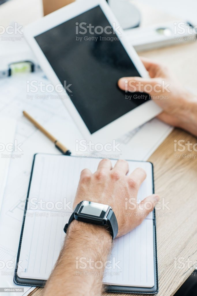 cropped shot of person wearing smartwatch and using digital tablet at workplace zbiór zdjęć royalty-free