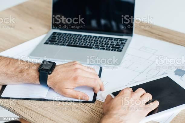 Foto de Cortada A Foto Da Pessoa Usando Smartwatch E Usando Tablet Digital No Local De Trabalho e mais fotos de stock de A caminho
