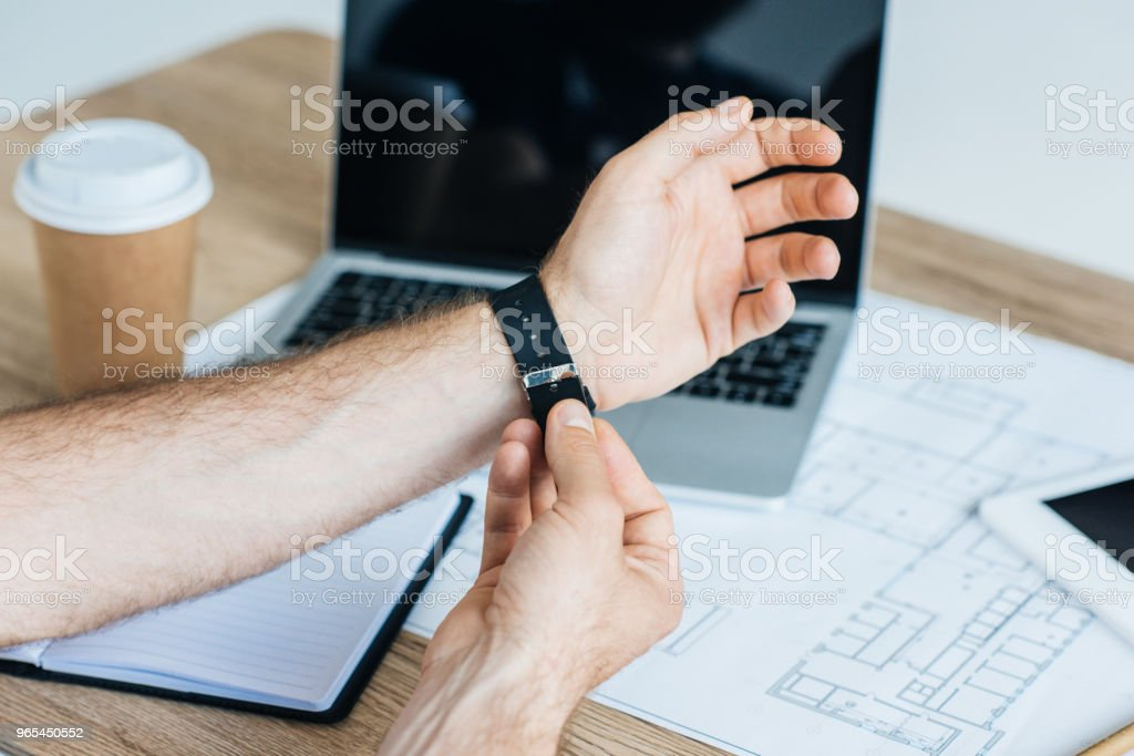 cropped shot of person wearing smartwatch at workplace royalty-free stock photo