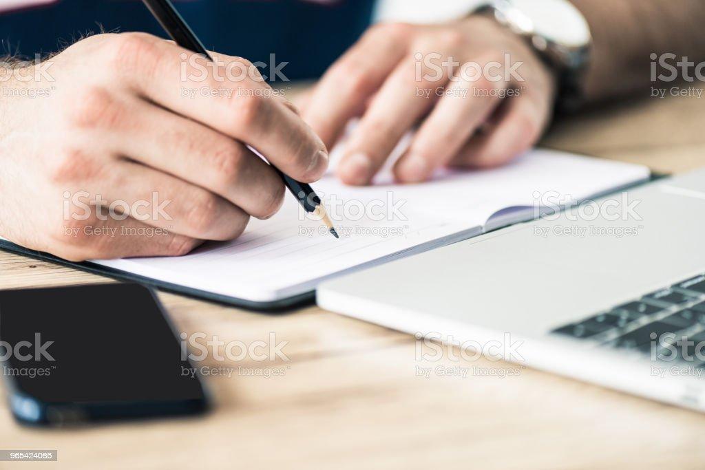 recadrée tir de personne écrire dans cahier à table en bois - Photo de Affaires libre de droits