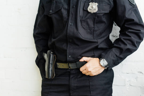 cropped shot of policeman standing in front of white brick wall cropped shot of policeman standing in front of white brick wall police uniform stock pictures, royalty-free photos & images