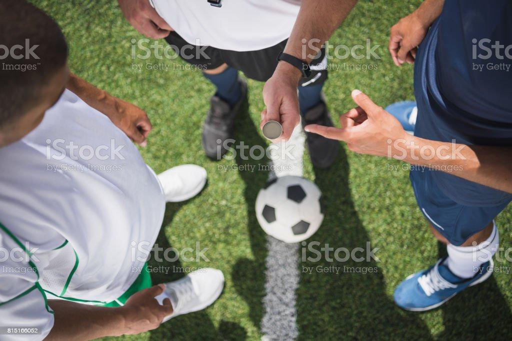 photo recadrée d'arbitre tenant la pièce avant le début du match de football sur terrain - Photo