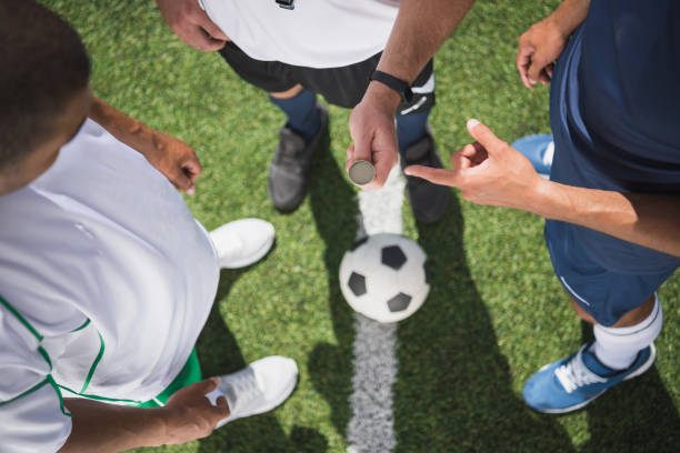 cropped shot of referee holding coin before start of soccer match on pitch cropped shot of referee holding coin before start of soccer match on pitch referee stock pictures, royalty-free photos & images