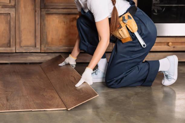 cropped shot of repairwoman installing laminate onto kitchen floor stock photo