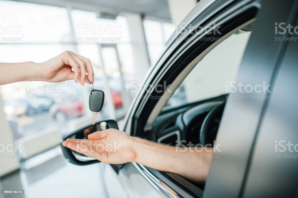 Cropped shot of seller giving key to man sitting in car at showroom stock photo