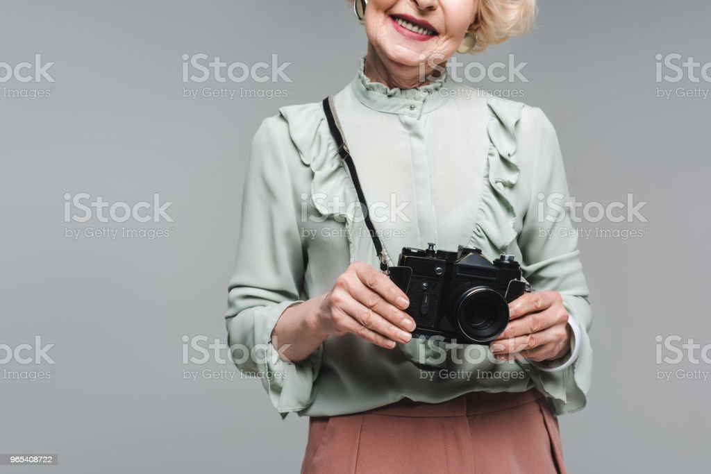 cropped shot of senior woman with vintage film camera isolated on grey royalty-free stock photo