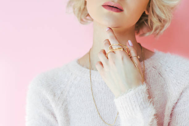 cropped shot of sensual young woman holding jewelry in hand isolated on pink stock photo
