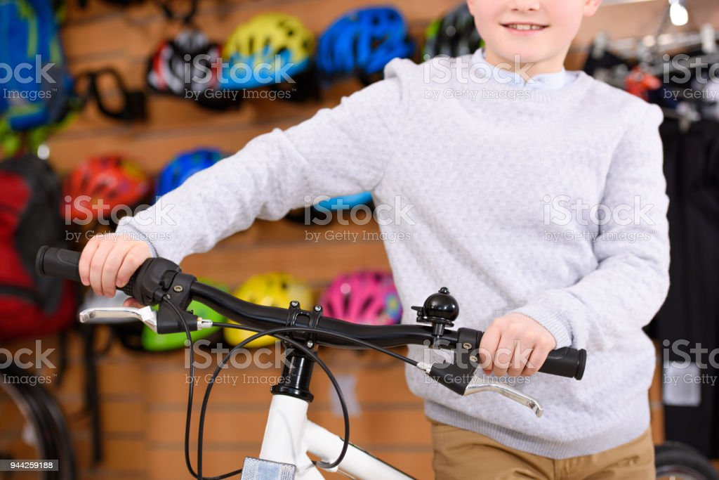 Cropped Shot Of Smiling Little Boy Standing With Bicycle In