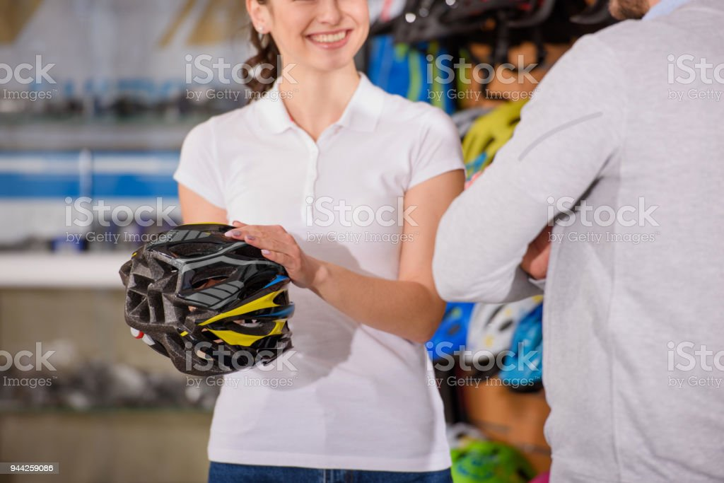 Cropped Shot Of Smiling Seller Showing Bicycle Helmet To