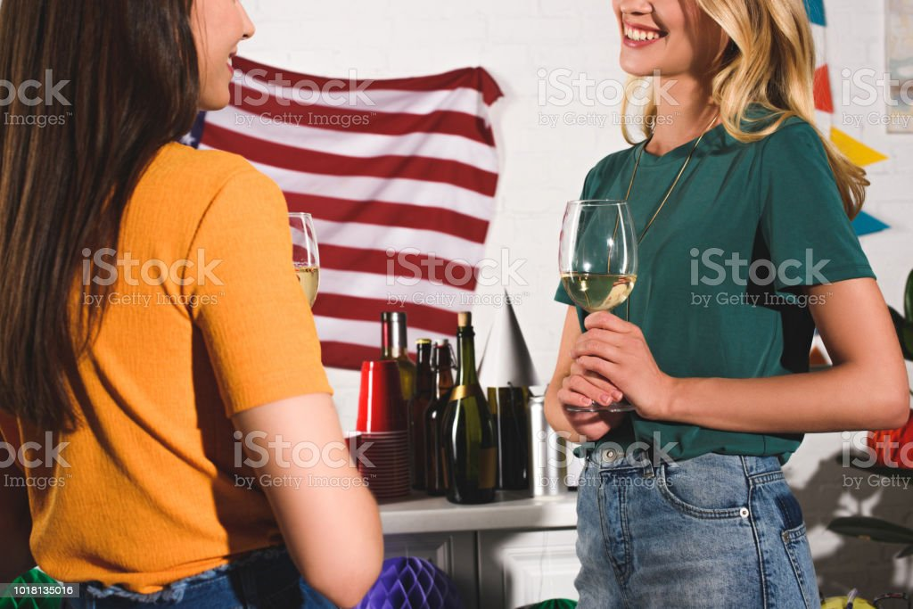 cropped shot of smiling young women drinking wine and talking at home party stock photo
