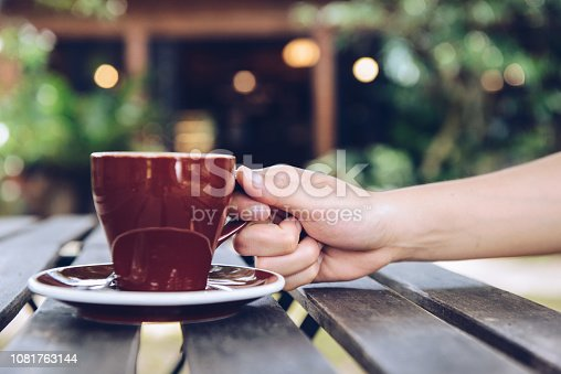 647209792 istock photo Cropped shot of someone hand touching a ceramic cup of coffee on the wood plank table with beautiful light bokeh in the background. 1081763144