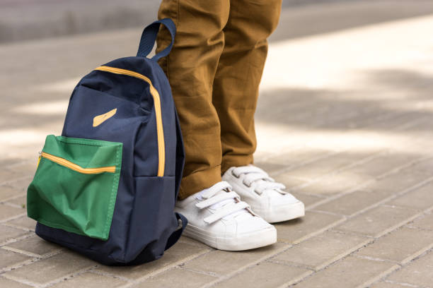 cropped shot of stylish schoolboy standing with backpack on street stock photo