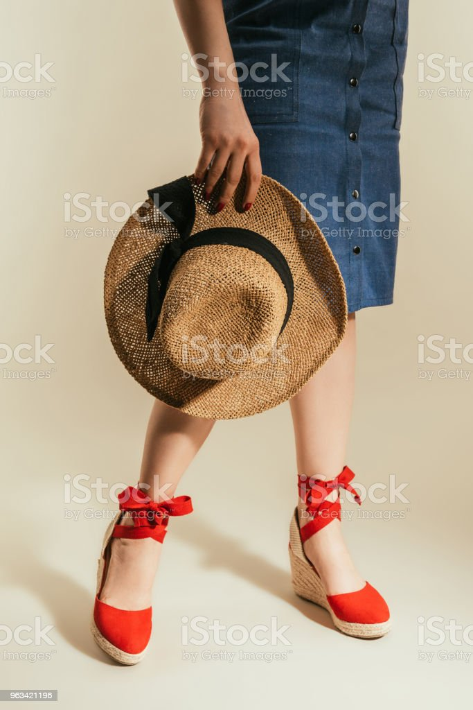cropped shot of stylish woman in red platform sandals holding straw hat on beige background - Zbiór zdjęć royalty-free (Beżowy)