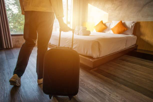 przycięte ujęcie turystki ciągnącej jej bagaż do jej sypialni hotelowej po zameldowaniu. - hotel zdjęcia i obrazy z banku zdjęć