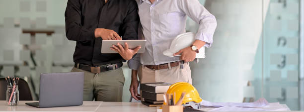 Cropped shot of two engineers working together with digital tablet, laptop and office supplies