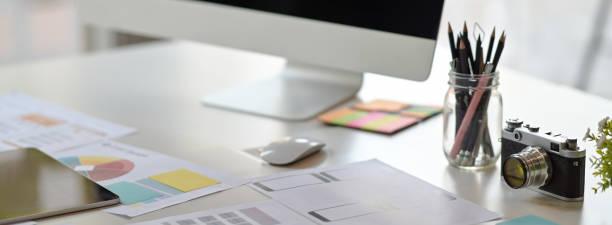 toma recortada del espacio de trabajo del desarrollador de la interfaz de usuario con computadora, papelería y papeleo - website design fotografías e imágenes de stock