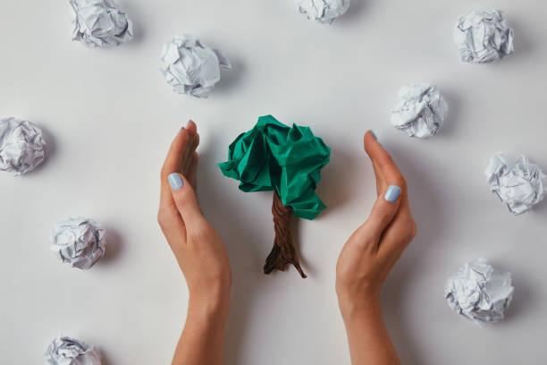 zugeschnittene Aufnahme für Frau zerknittert Papiere in Baumform auf weiße Fläche – Foto