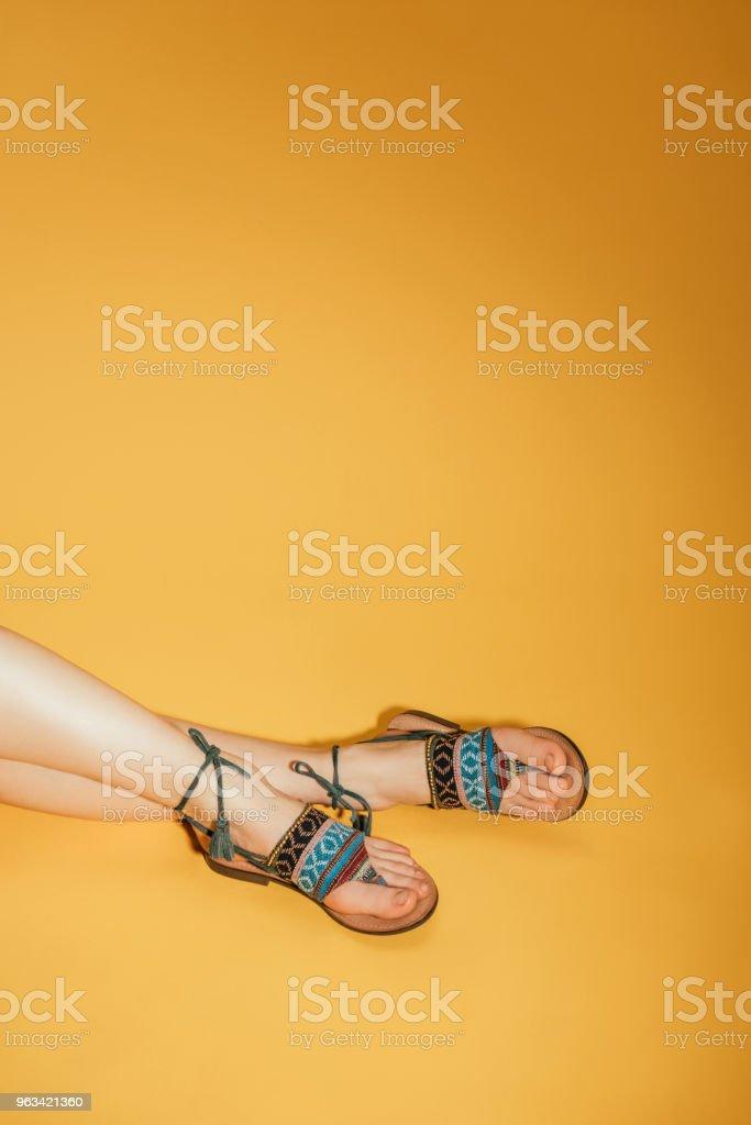 cropped shot of woman feet in stylish sandals on yellow background - Zbiór zdjęć royalty-free (Cięcie w lini dolnej)