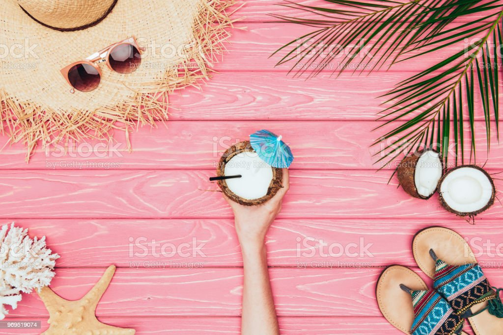 cropped shot of woman holding coconut cocktail  surrounded with various tropical travel attributes on pink wooden surface stock photo