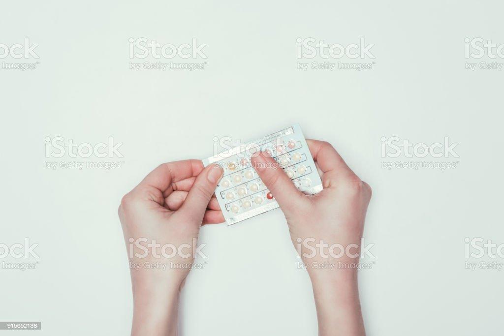 tiro recortado de mulher segurando pílulas contraceptivas em mãos isoladas em cinza - foto de acervo