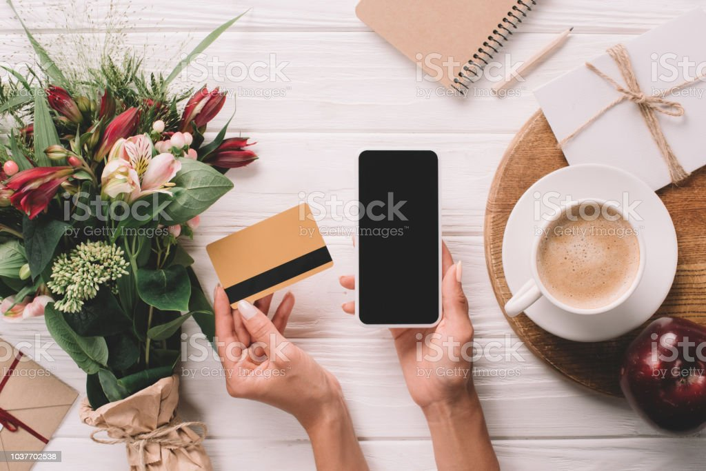 cropped shot of woman holding credit card and smartphone with blank screen at tabletop with bouquet of flowers and cup of coffee stock photo