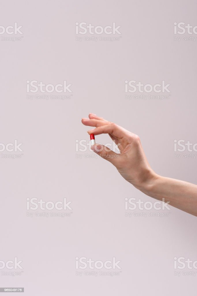 cropped shot of woman holding drug capsule isolated on grey royalty-free stock photo