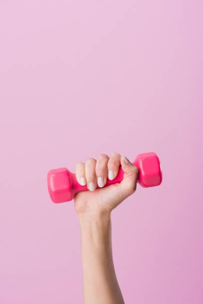 zugeschnittenen schuss frau mit kurzhantel isoliert auf rosa - rosa training stock-fotos und bilder