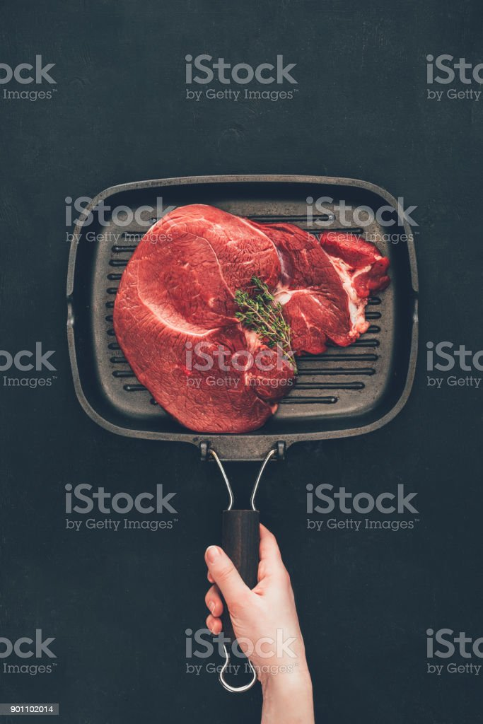 cropped shot of woman holding grill pan with raw steak stock photo