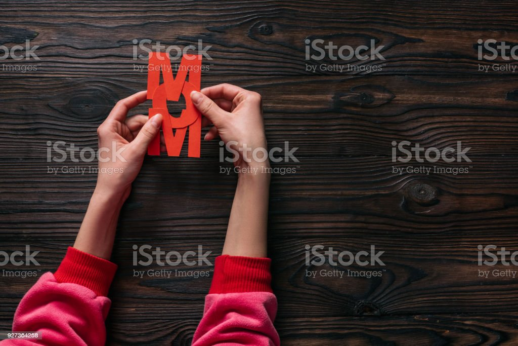 cropped shot of woman holding mom lettering in hands cropped shot of woman holding mom lettering in hands Adult Stock Photo