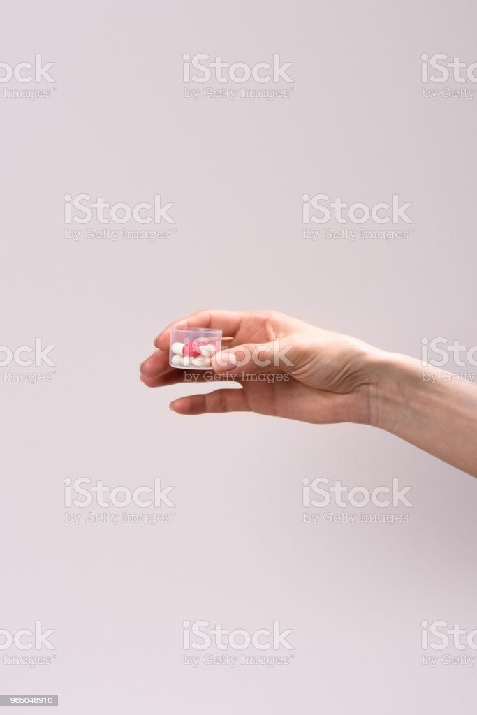 cropped shot of woman holding plastic container of pills isolated on grey royalty-free stock photo