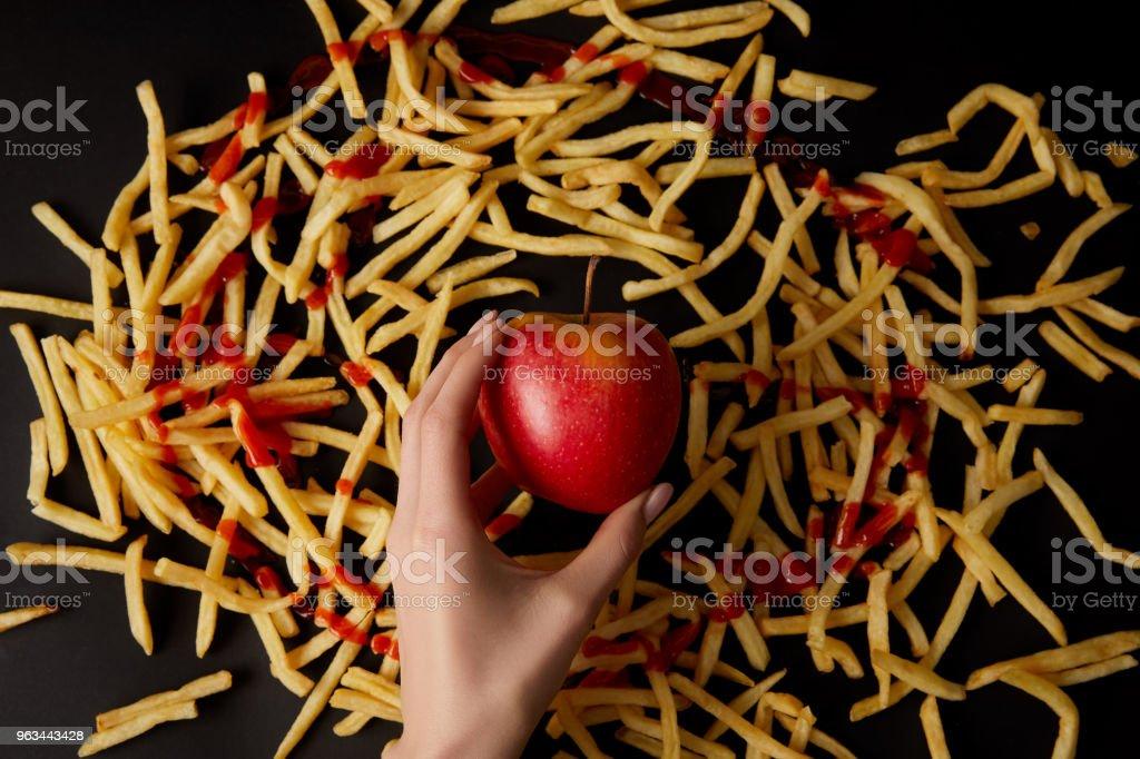 photo recadrée de femme tenant une pomme rouge entourée de fries français isolé sur fond noir - Photo de Adulte libre de droits