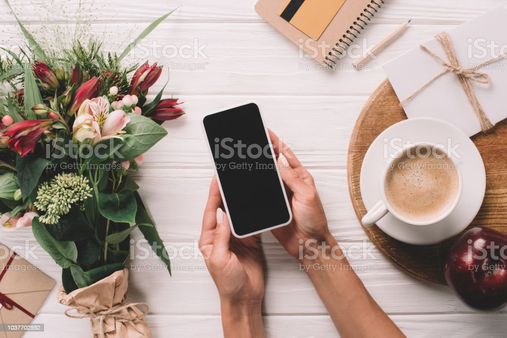 cropped shot of woman holding smartphone with blank screen at surface with wrapped bouquet of flowers and cup of coffee stock photo