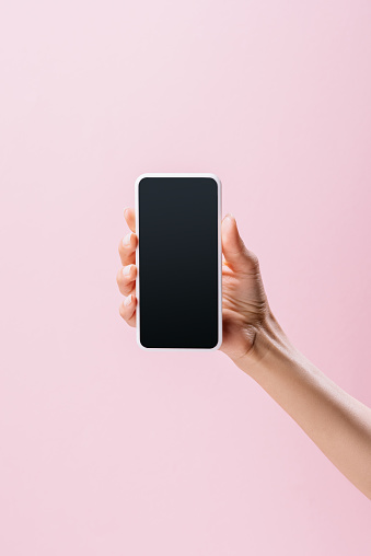 cropped shot of woman holding smartphone with blank screen isolated on pink
