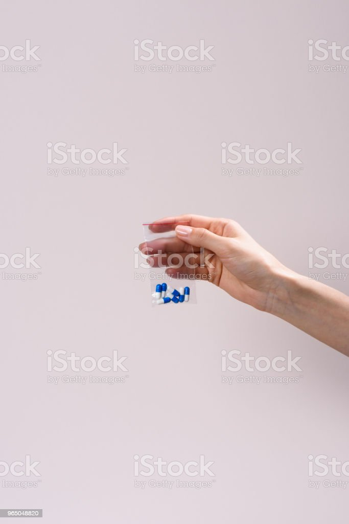 cropped shot of woman holding zip bag with pills isolated on grey zbiór zdjęć royalty-free
