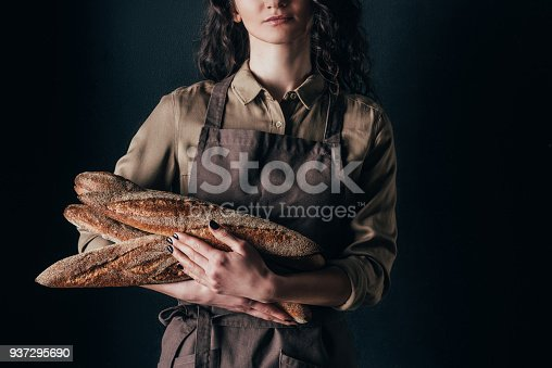 istock cropped shot of woman in apron holding french baguettes in hands isolated on black 937295690