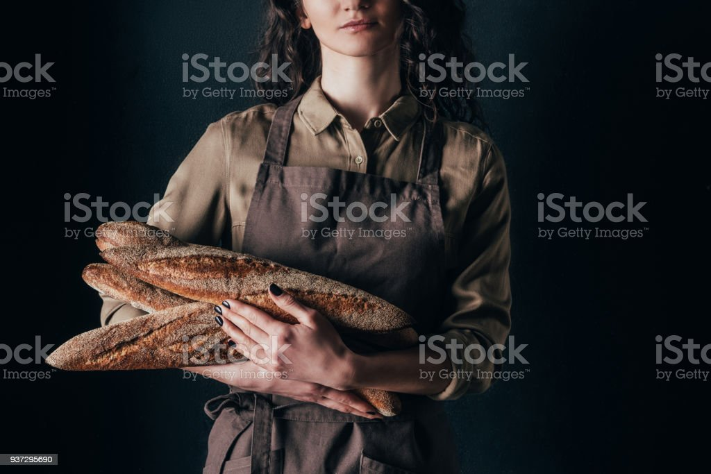 cropped shot of woman in apron holding french baguettes in hands isolated on black stock photo