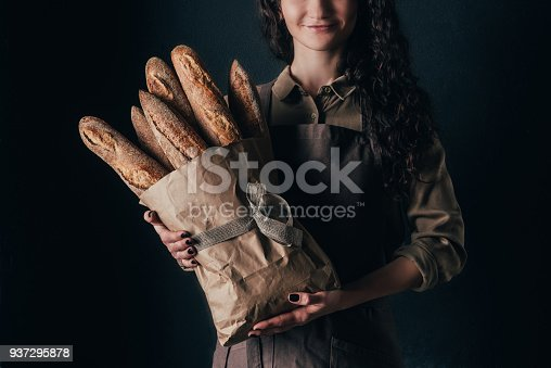 istock cropped shot of woman in apron holding french baguettes in paper bag in hands isolated on black 937295878